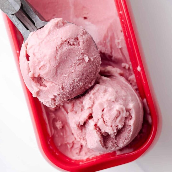 Overhead of water melon sorbet in ice cream container.